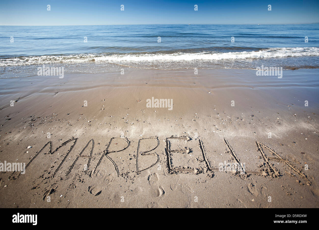 the word Marbella written in the wet sand  at the beach - Stock Image