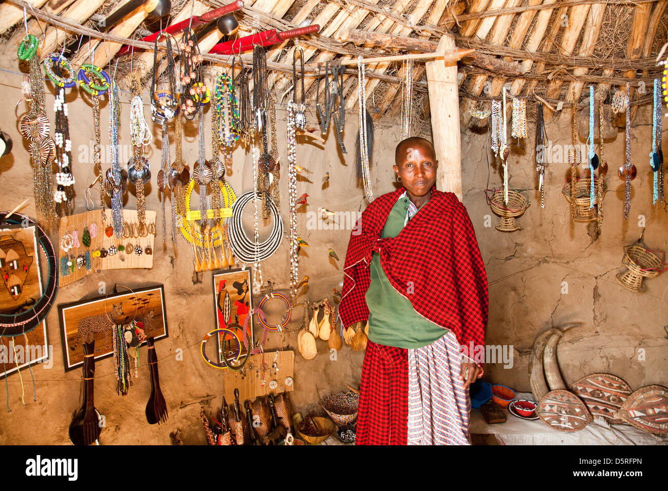 Africa, Tanzania;Maasai women in traditional dress in her souvenir stand with hand made jewelry - Stock Image