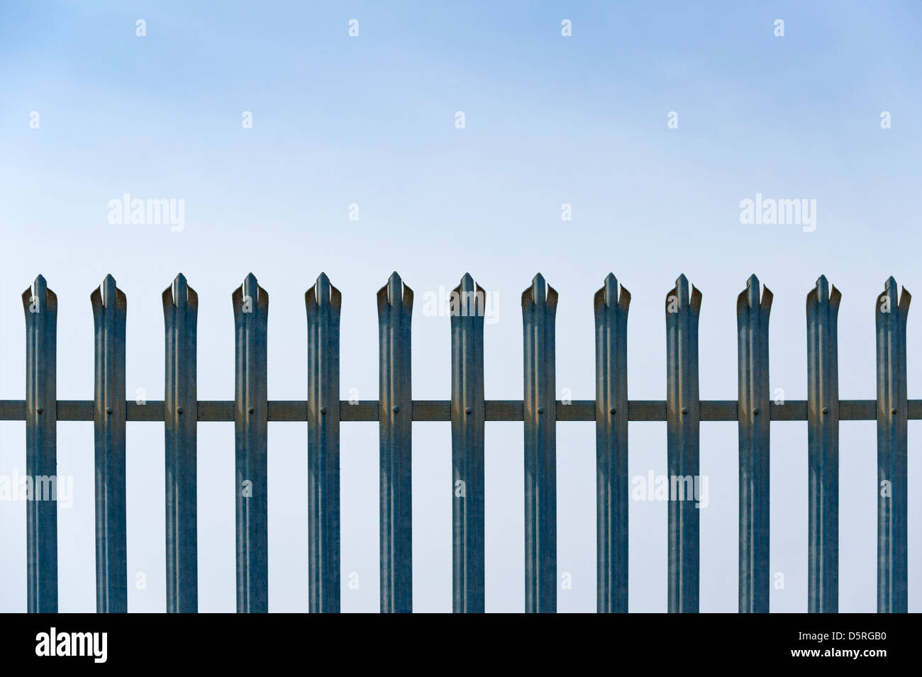 Spiked Security Fence Against a blue sky. Concept - Stock Image