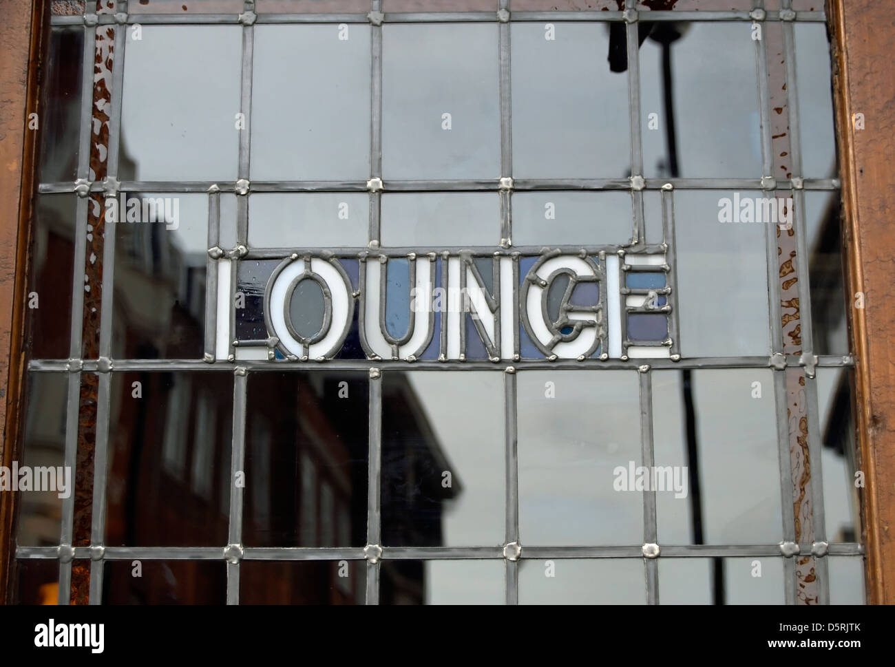 the word lounge set into a leaded light window on a door leading to the lounge bar of a pub, richmond , surrey, - Stock Image