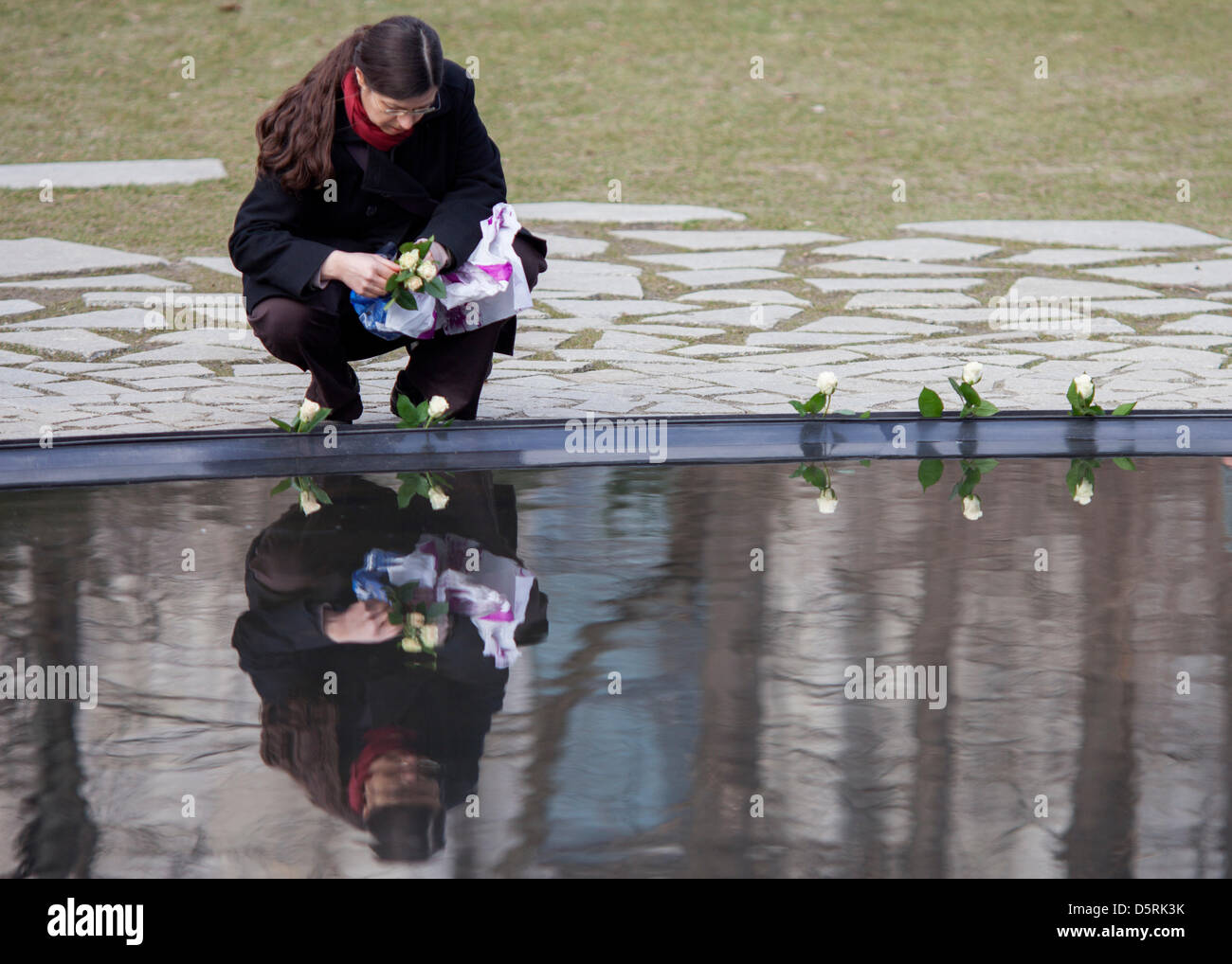 A woman lays a flowers at the monument for the Sinti and Roma murderd by the Nazis in Berlin,Germany, 08April - Stock Image