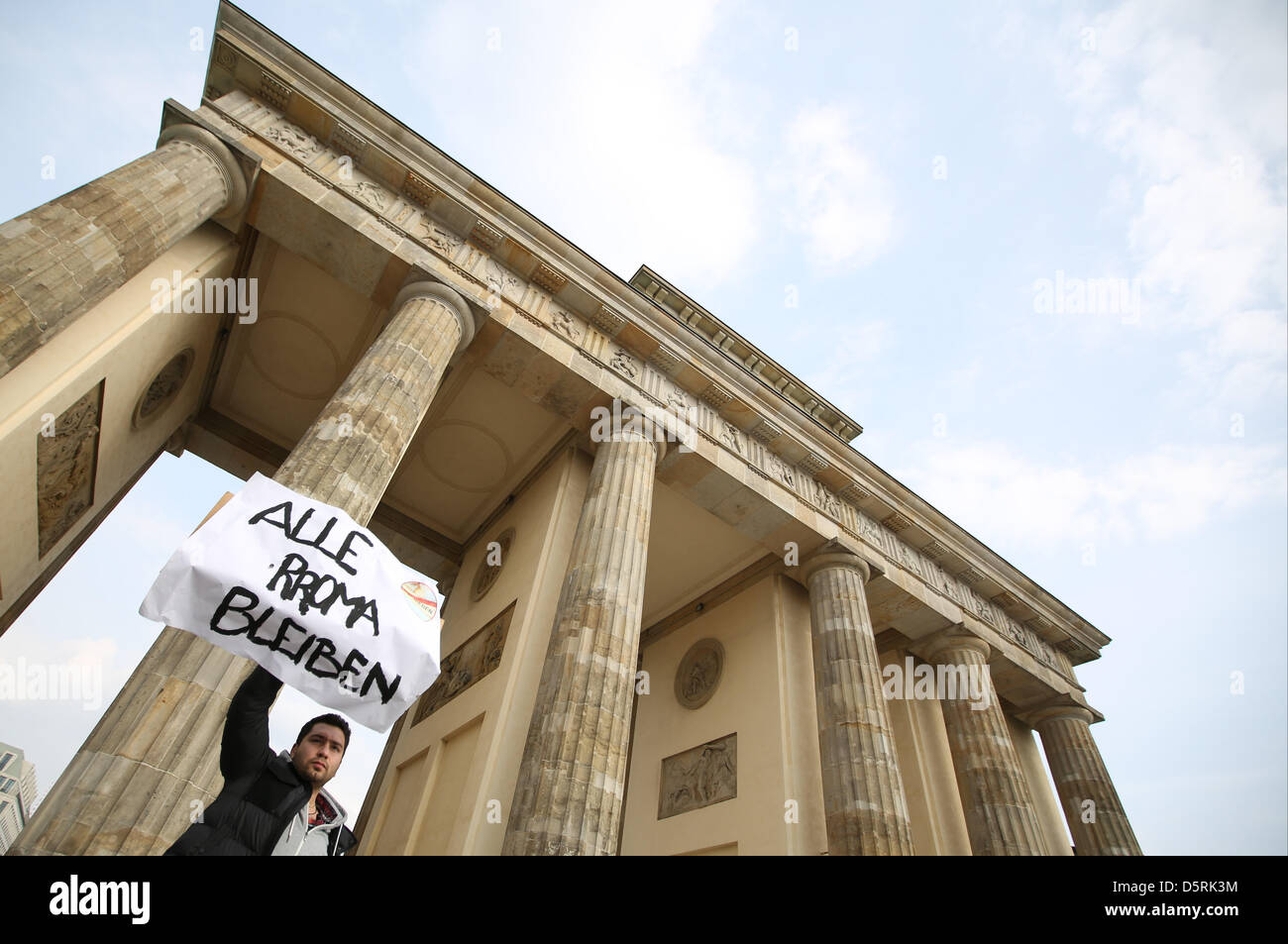 'All Roma will stay' is written on a placard held by a demonstrator at the Brandenburg Gate in Berlin,Germany, - Stock Image