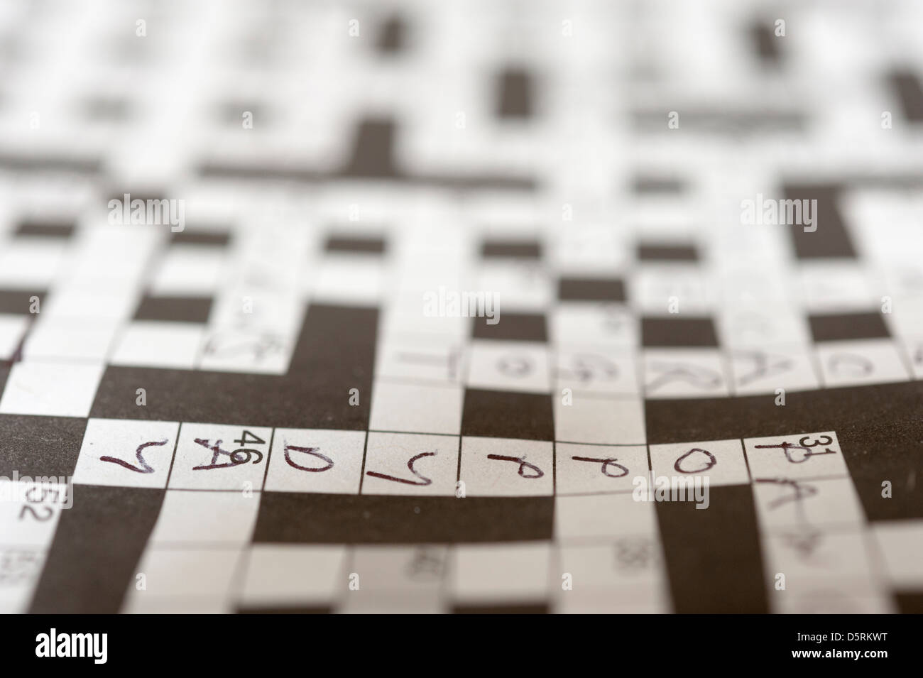 Close up of crossword puzzle with word poppy day visible. Selective focus so that only one word is in focus - Stock Image