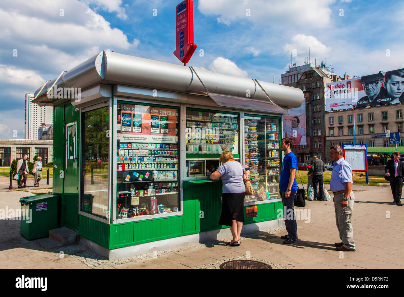 People at a typical kiosk selling tobacco, tickets and magazines in downtown Warsaw, Poland. - Stock Image