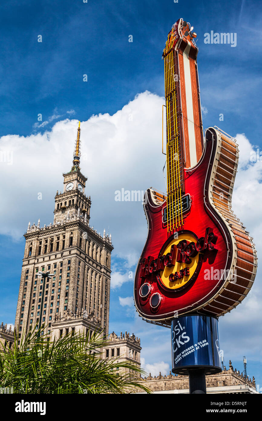 Iconic symbols of opposing political philosophies, Palace of Culture and Science, and Hard Rock Cafe guitar in Warsaw,Poland. - Stock Image