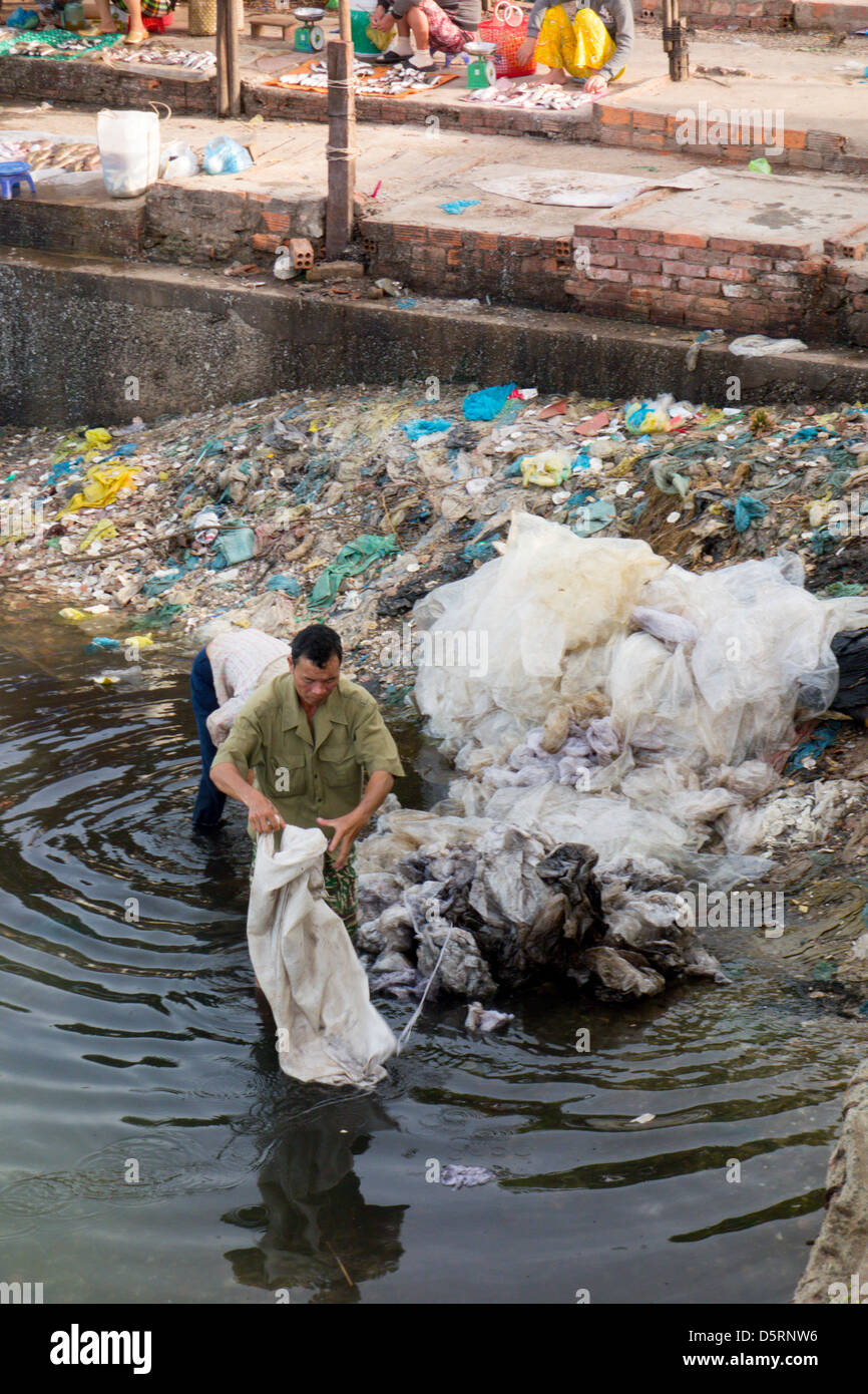 collecting garbage in river near waterfront market; Phan Thiet; Vietnam - Stock Image