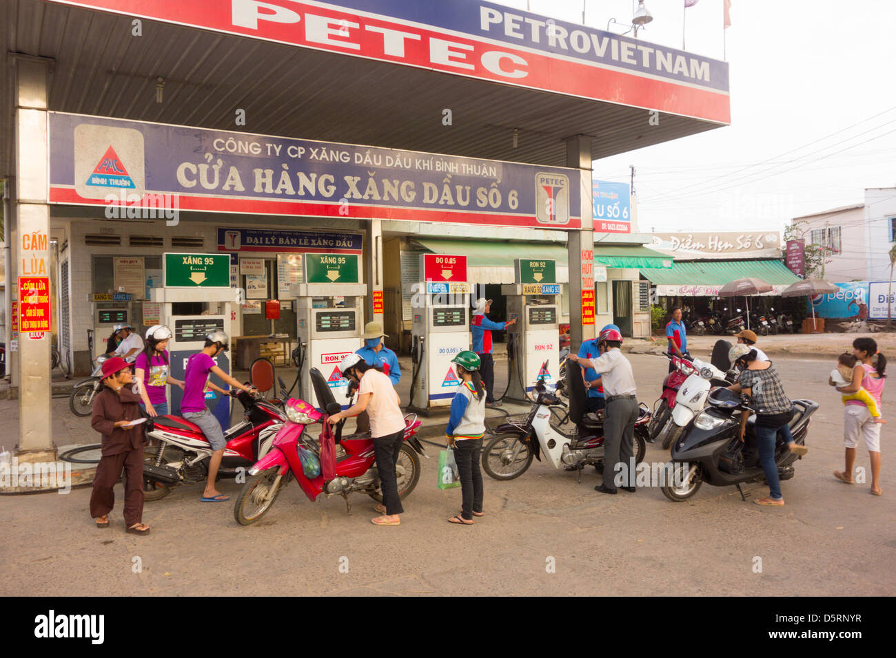 Motor scooters fill up at gas station in town of Phan Thiet Vietnam - Stock Image
