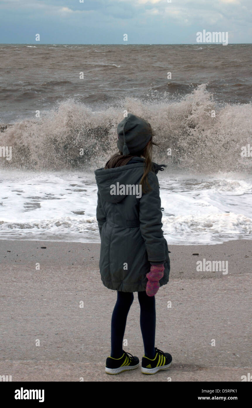 Easter weekend 2013. Icy cold wintry weather. Girl wrapped up in warm clothes, watching the waves crash on Babbacome - Stock Image