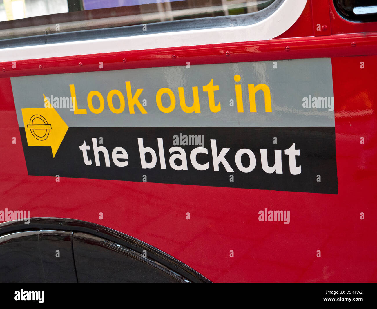 Restored historic traditional red London bus with WW2 poster 'Look out in the Blackout' - Stock Image
