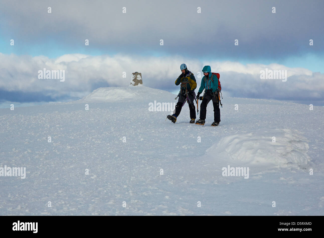 Two climbers with ice axes on the summit of Ben Nevis in snow conditions - Stock Image