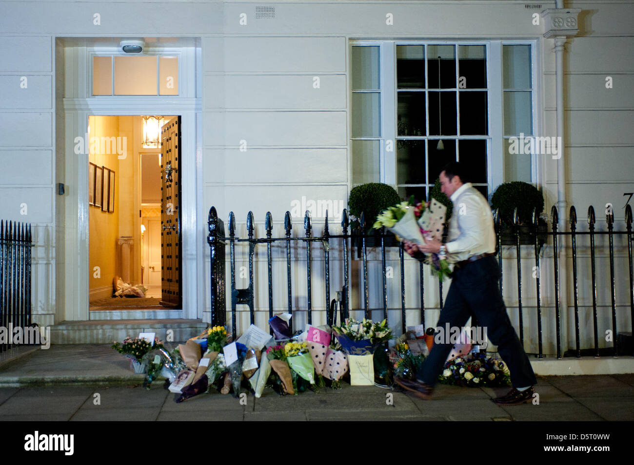 London,UK. 8th April 2013. Flower tributes are collected and brought inside the residence of Margaret Thatcher in - Stock Image