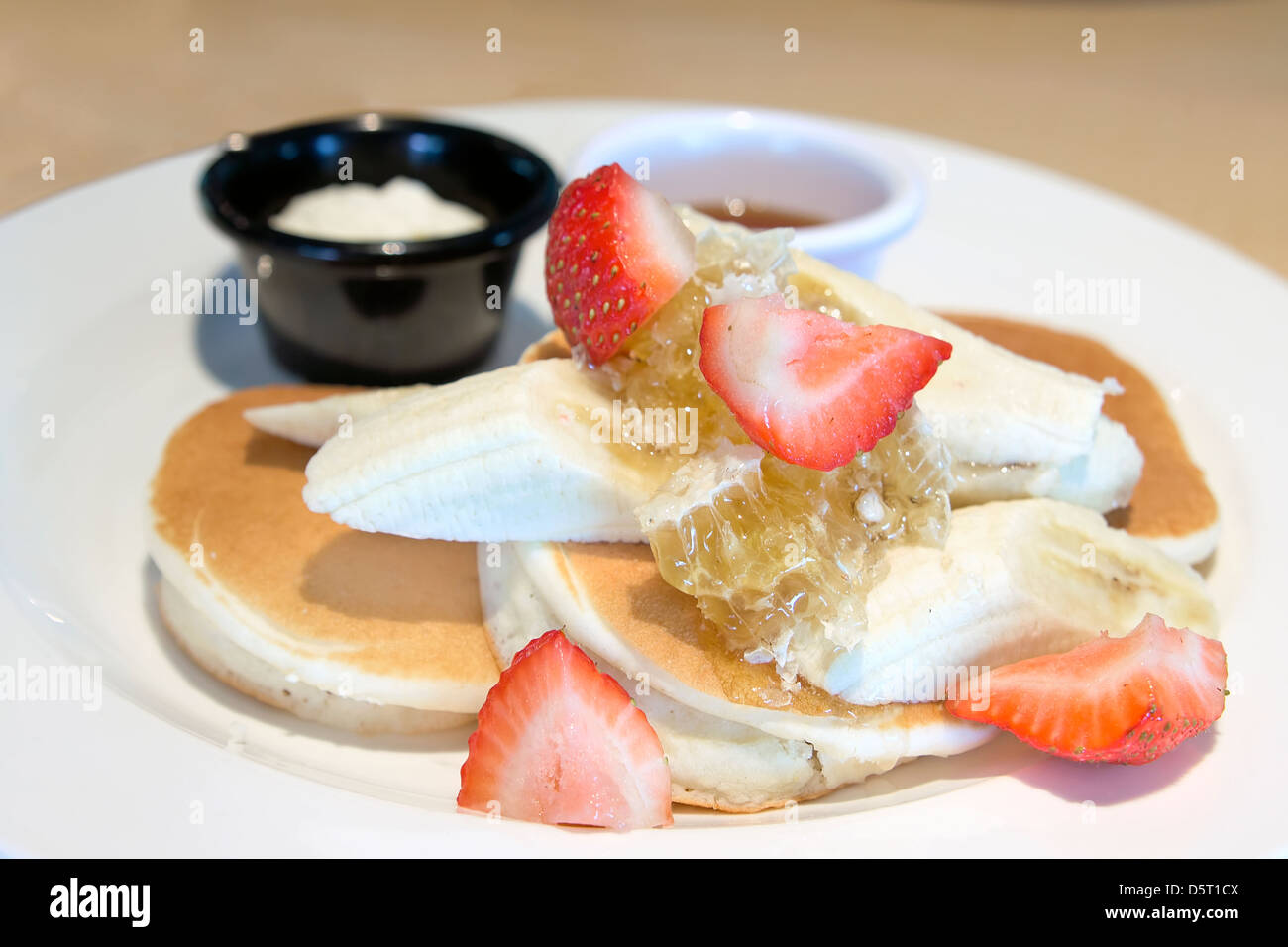 Pancakes with Bananas Strawberries Honeycomb Maple Syrup and Butter Closeup - Stock Image