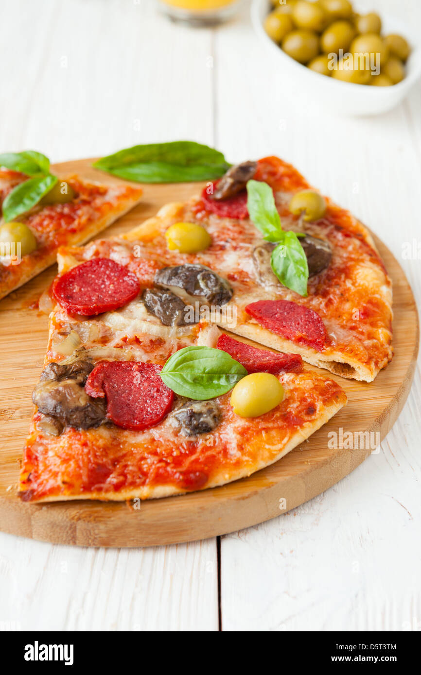 sliced pizza with cheese and salami on board, and basil - Stock Image