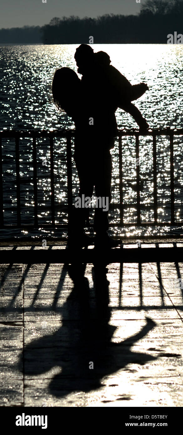 The silhouette of a woman and child are pictured in the back-lighting at Maschsee Lake in Hanover,Germany, 20 November Stock Photo