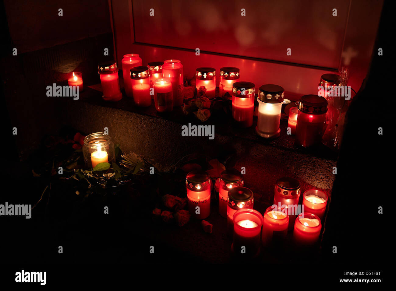 Friends and neighbours have placed candles in front of the door of a house in which a family drama took place in - Stock Image