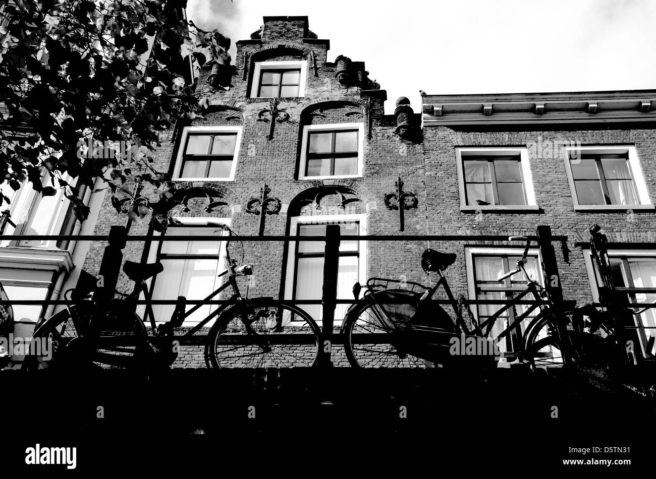 Bicycles parked on a bridge in front of an old canal house, Oude Gracht, Utrecht, the Netherlands Stock Photo