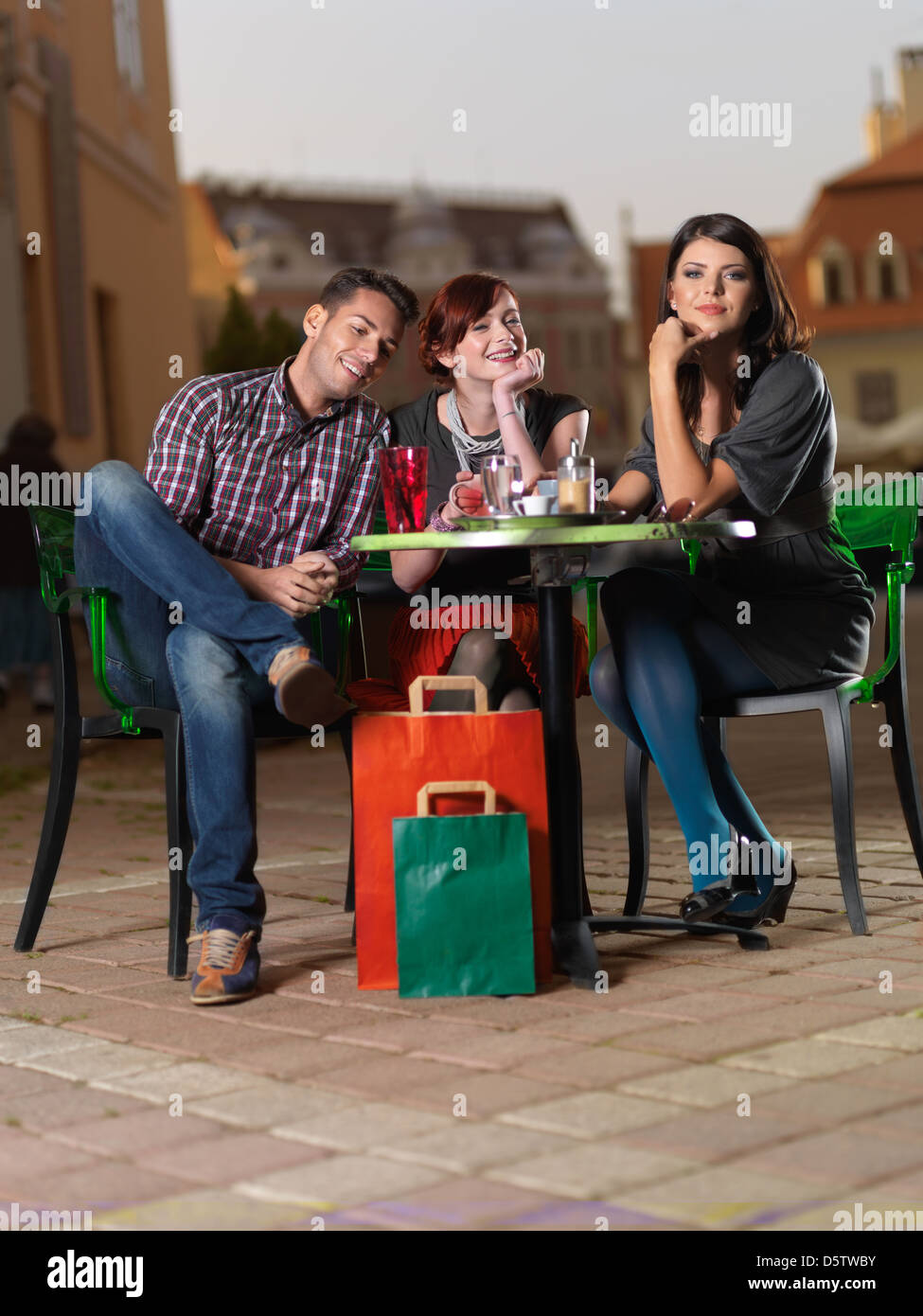 young beautiful man and gorgeous women at a coffee downtown on terrace - Stock Image