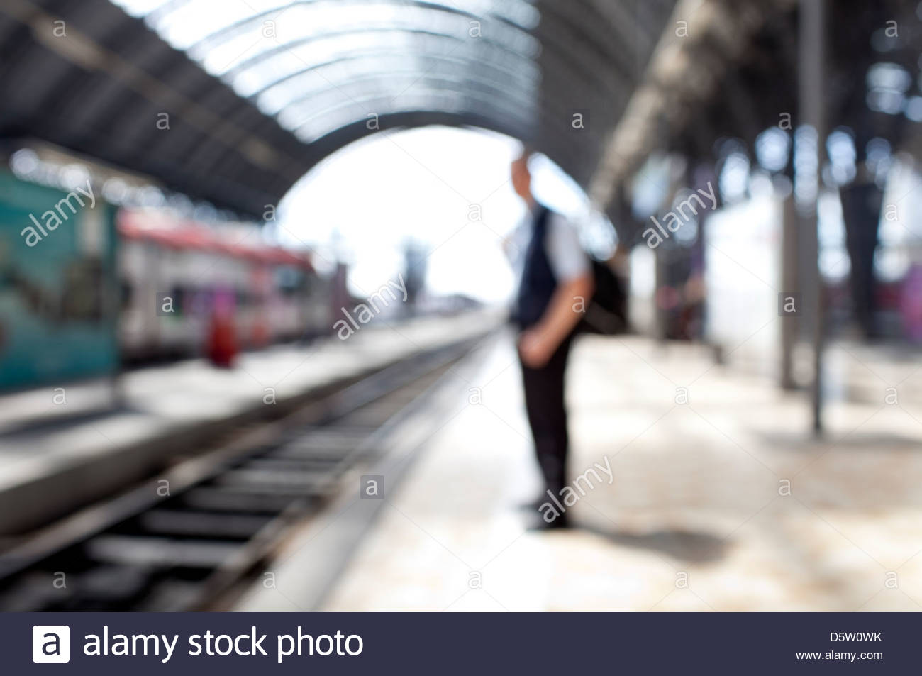 Man standing at a rail track - Stock Image