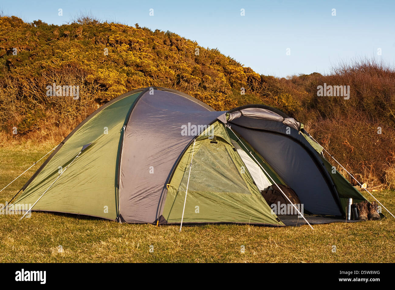 dome tent pitched in field for wild camping in the great outdoors with front flap open showing interior - Stock Image