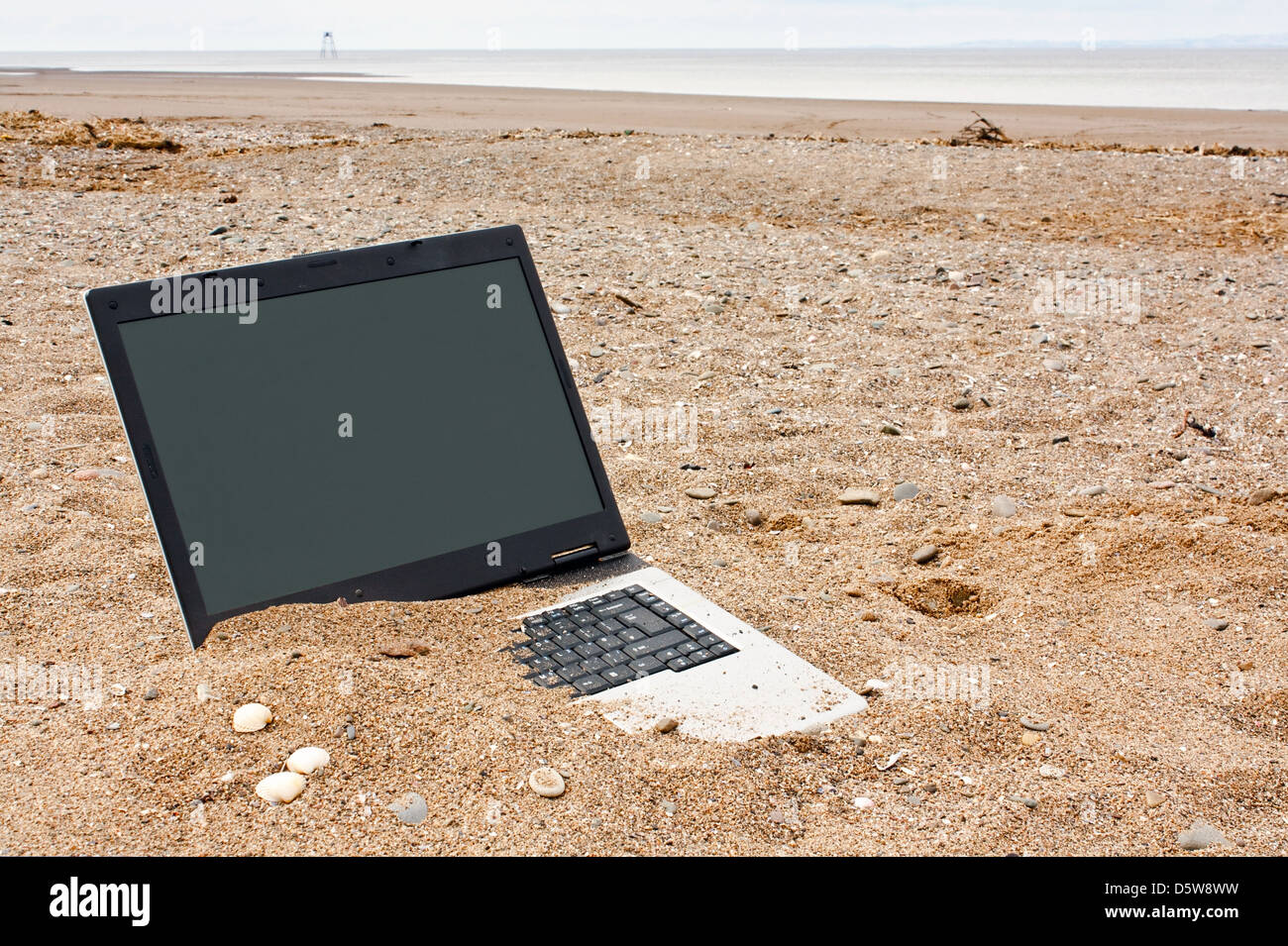 obsolete laptop personal computer at the beach good concept for out of date technology or for travel websites - Stock Image