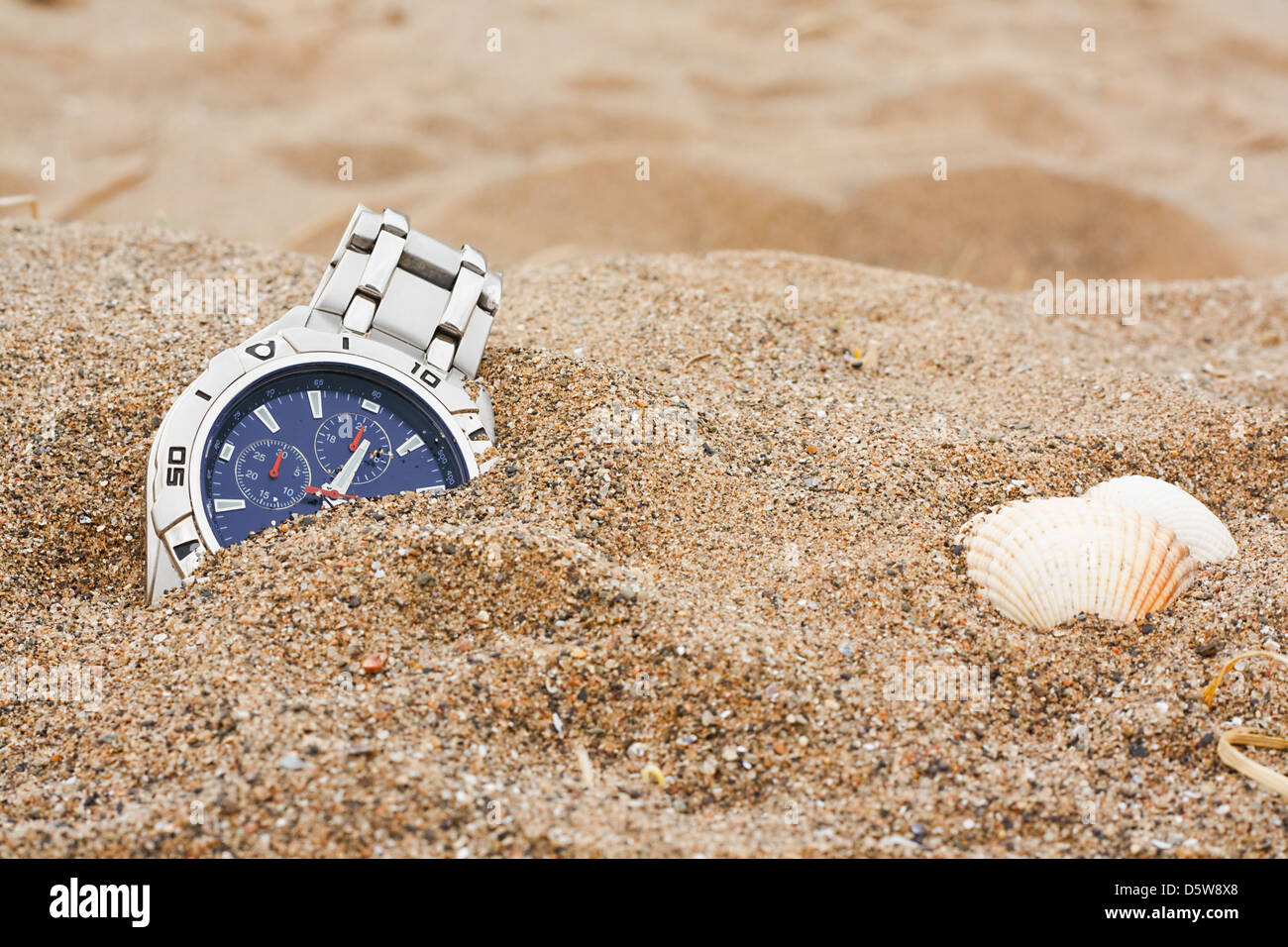 wristwatch left discarded at the beach great for lost property or travel insurance - Stock Image