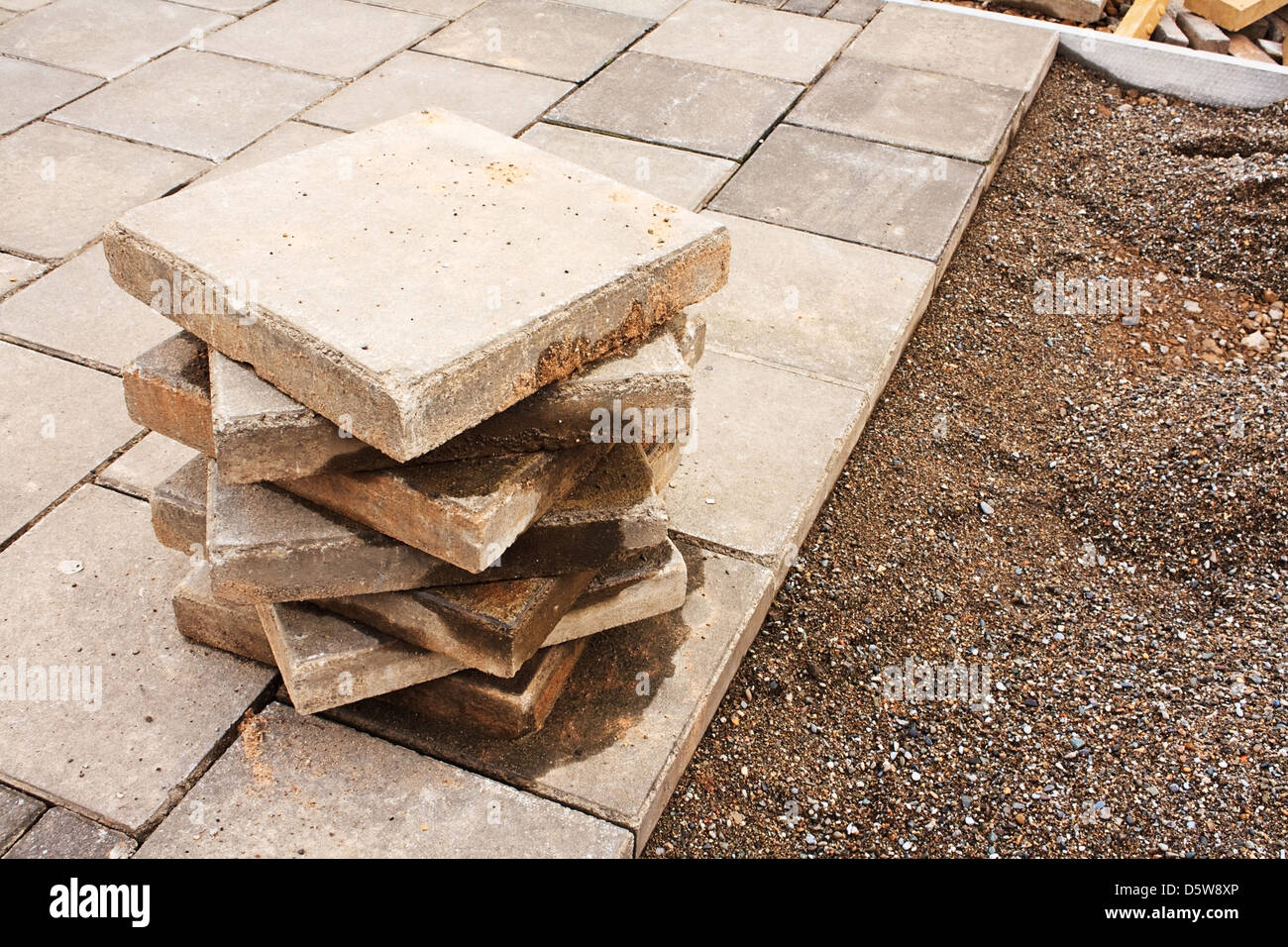 commercial paving in progress laying new pavement at the side of a busy road - Stock Image