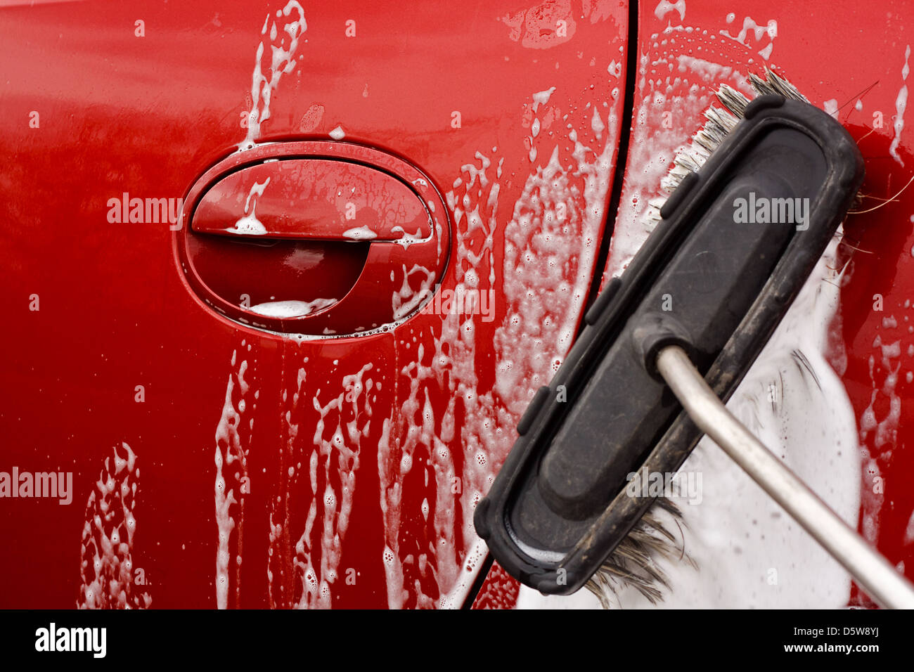 Washing the car with a soapy brush at a coin operated car jet wash - Stock Image