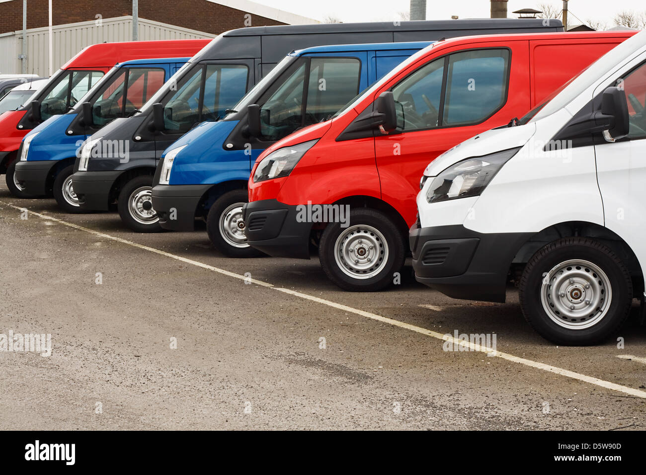 row of different marques of commercial vehicles or vans for retail sale on a motor dealers lot all logos removed - Stock Image