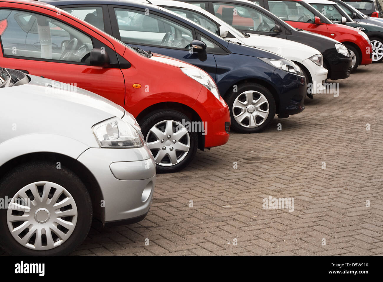 row of different european marques of used cars for retail sale on a motor dealers forecourt all logos removed - Stock Image