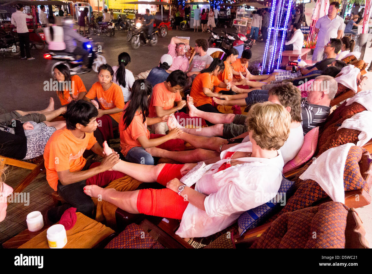 Masseurs and masseuses massage tourists on street at night in Pub Street nightlife district Siem Reap Cambodia - Stock Image