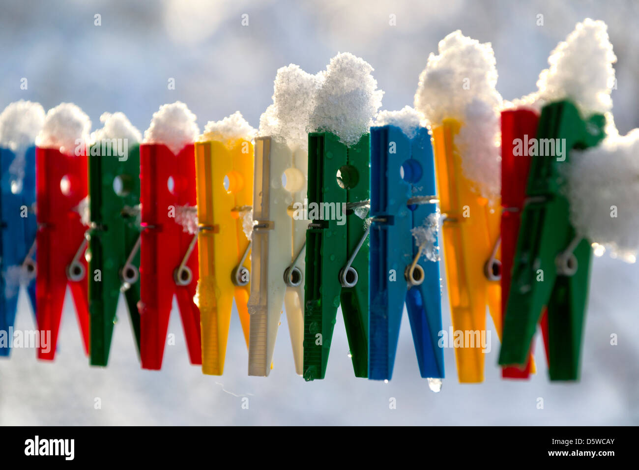 Washing line with a row of colorful pegs covered with snow queued in a row - Stock Image