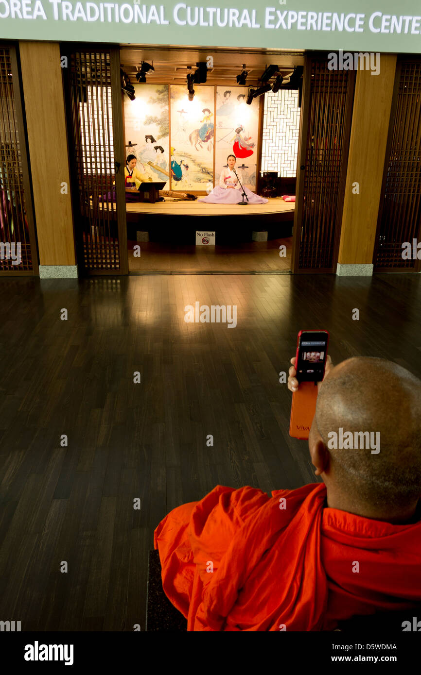 Thai Buddhist monk photographs traditional Korean musician with his cell phone in Incheon Airport; Seoul; Korea - Stock Image