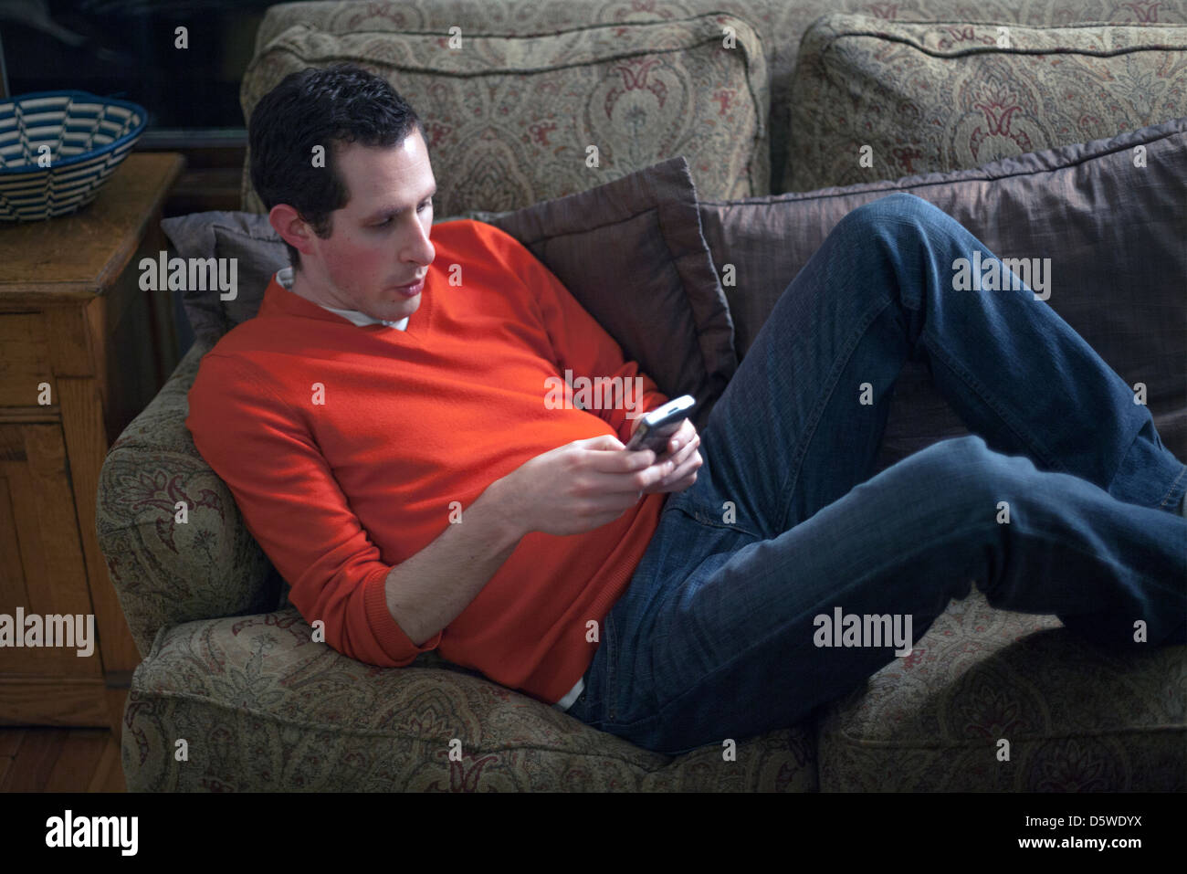 A man checks his e-mail on his mobile device in his living room. - Stock Image