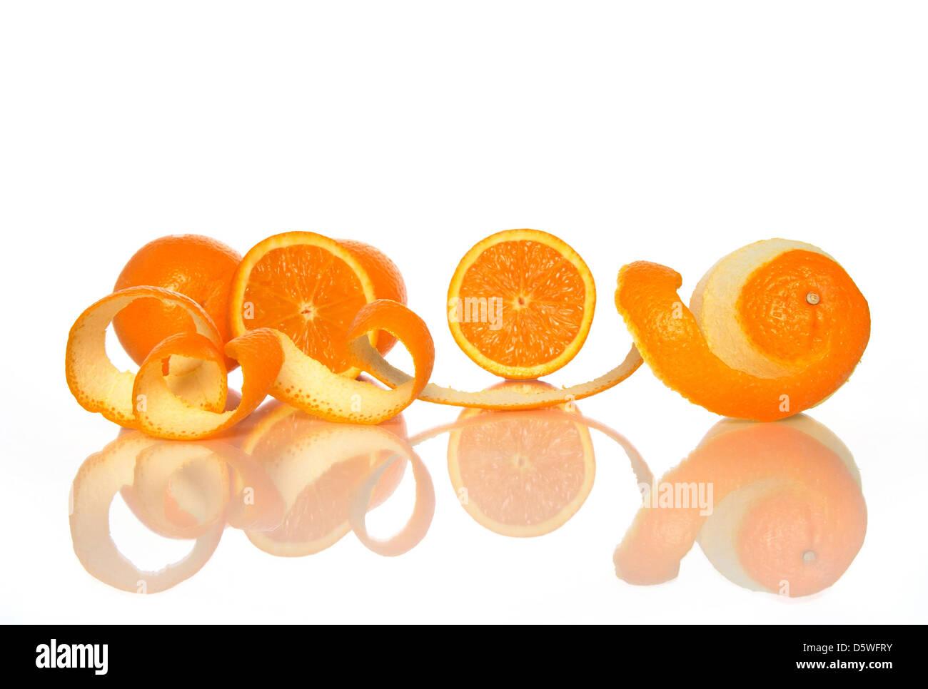Tasty oranges and spiral orange peel reflecting on white background. - Stock Image