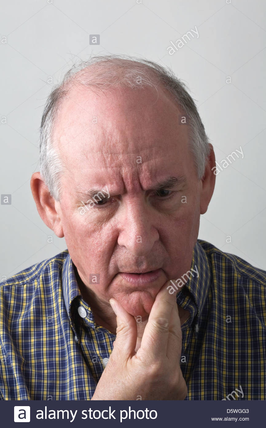 Senior man in checked shirt looking very thoughtful. - Stock Image