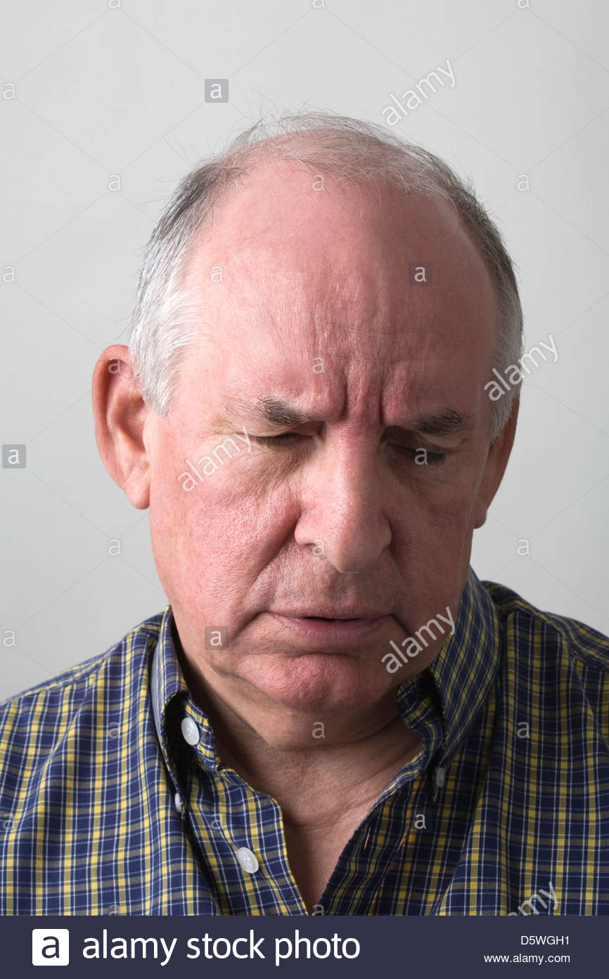Senior man in check shirt looking down and worried. - Stock Image