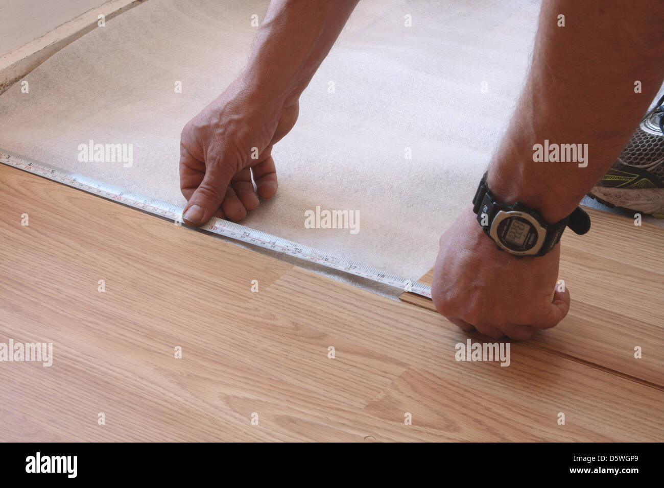 A Man Is Measuring A Strip Of Laminate In Preparation For