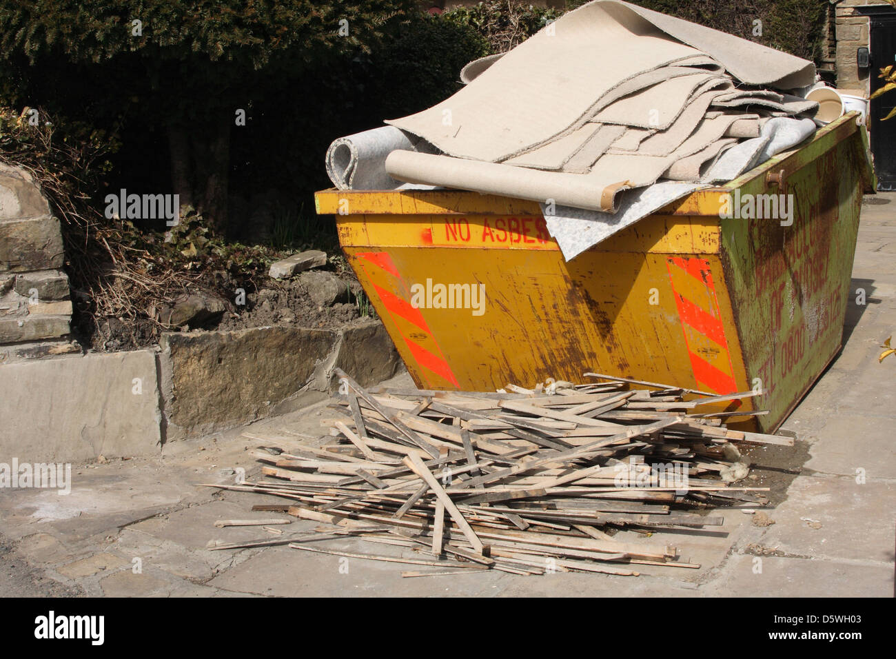 A skip overflowing with rubbish thrown out after a home renovation - Stock Image