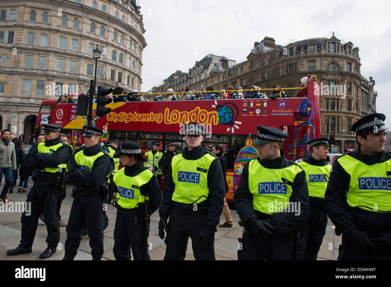 A quirky shot of a line of police and a sightseeing bus at a protest against the Bedroom Tax on 30th March 2013 - Stock Image