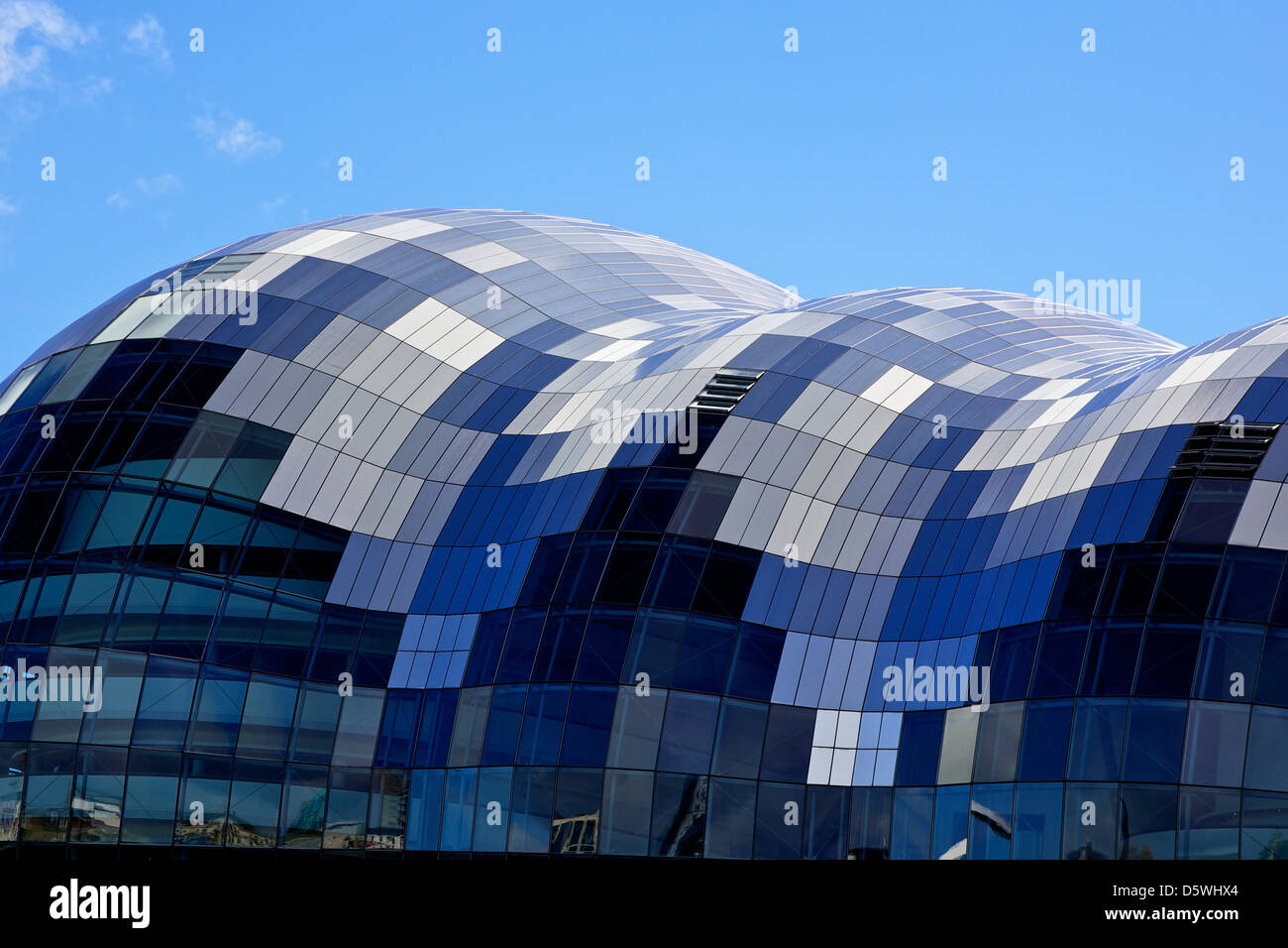 The Sage, Gateshead with the curved glass roof reflecting the blue of the sky and the white of the clouds. - Stock Image