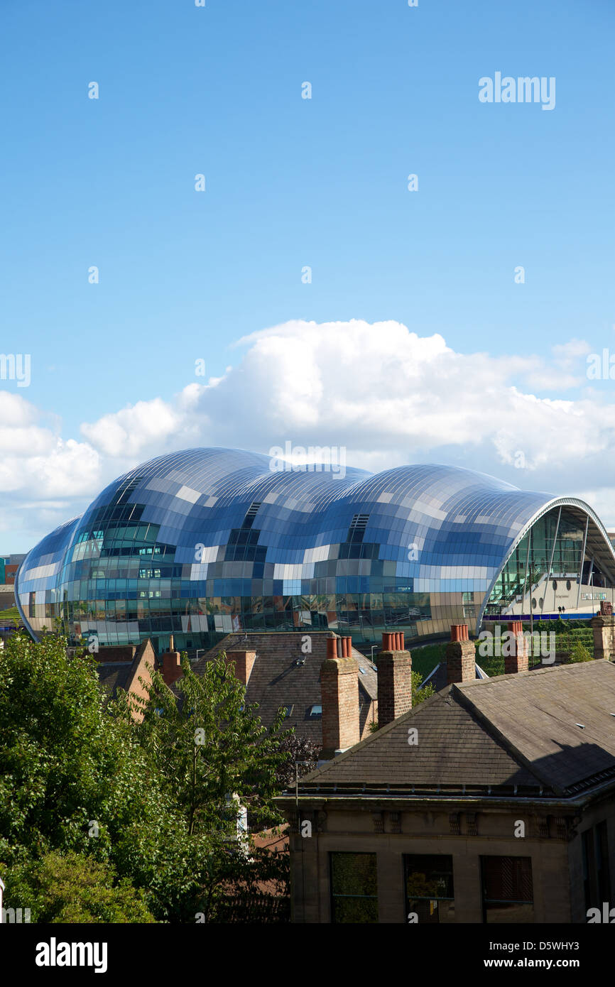 The Sage, Gateshead with the tall chimneys of the city housing in the foreground. - Stock Image