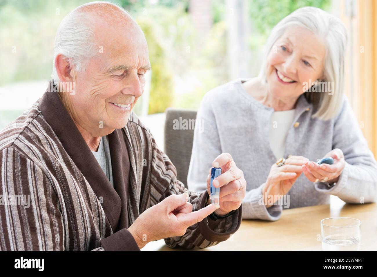 Older couple testing blood sugar together - Stock Image