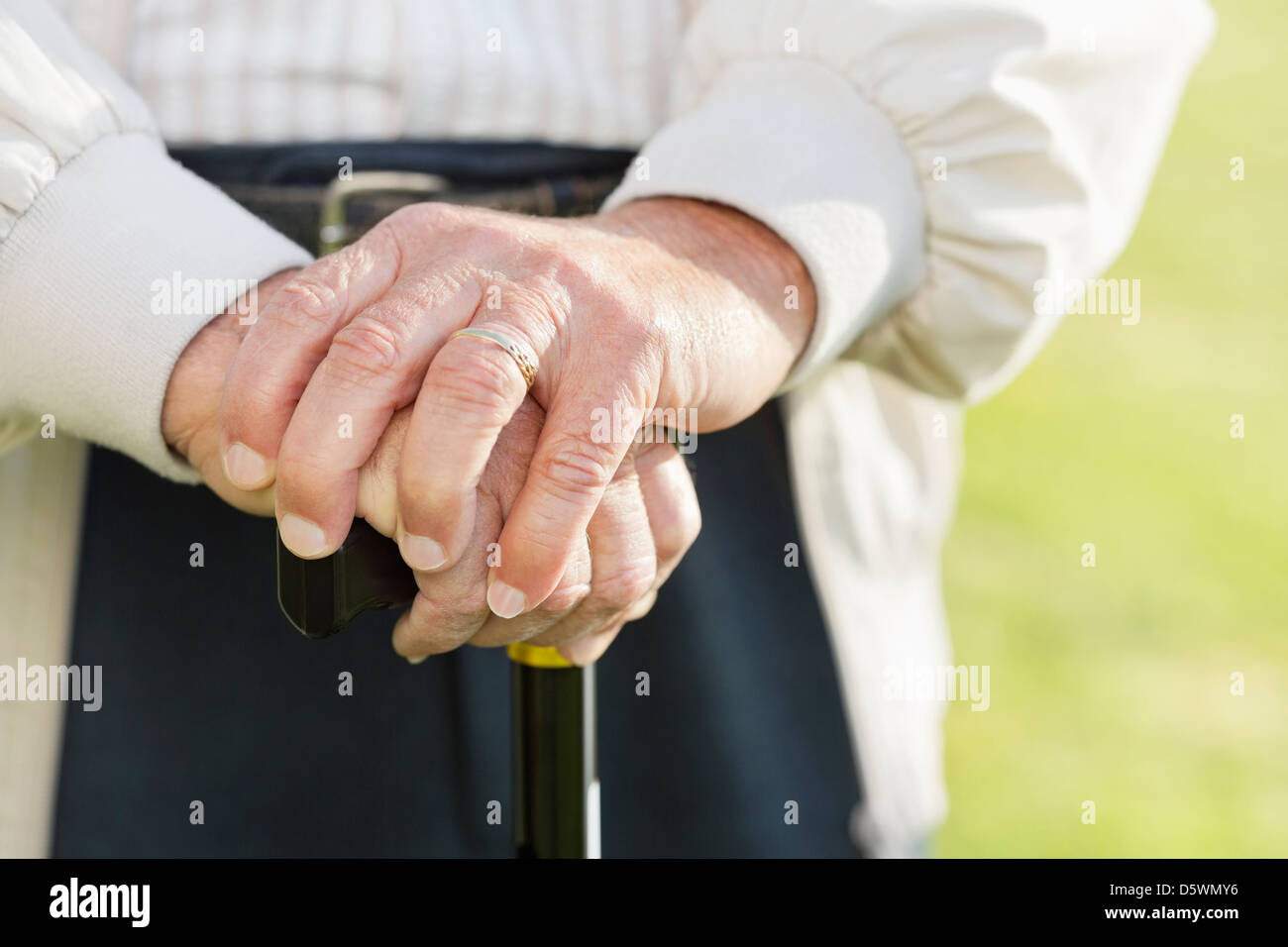 Close up of older man's hands on cane - Stock Image