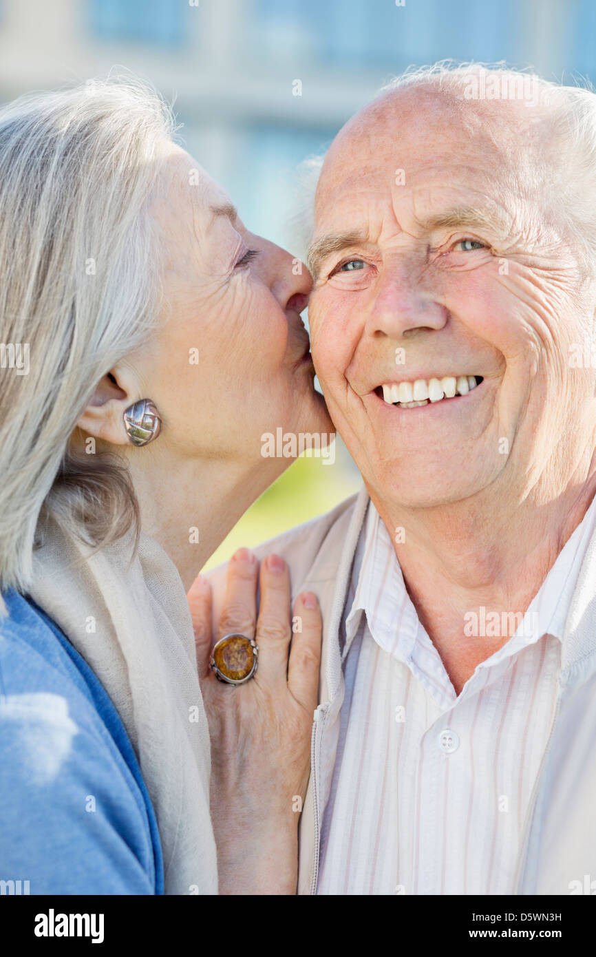 Smiling older couple kissing outdoors - Stock Image