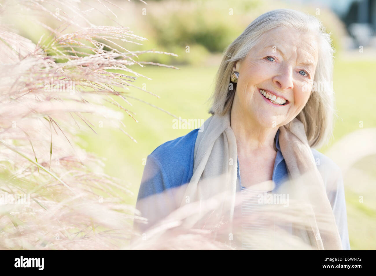 Older woman smiling outdoors - Stock Image