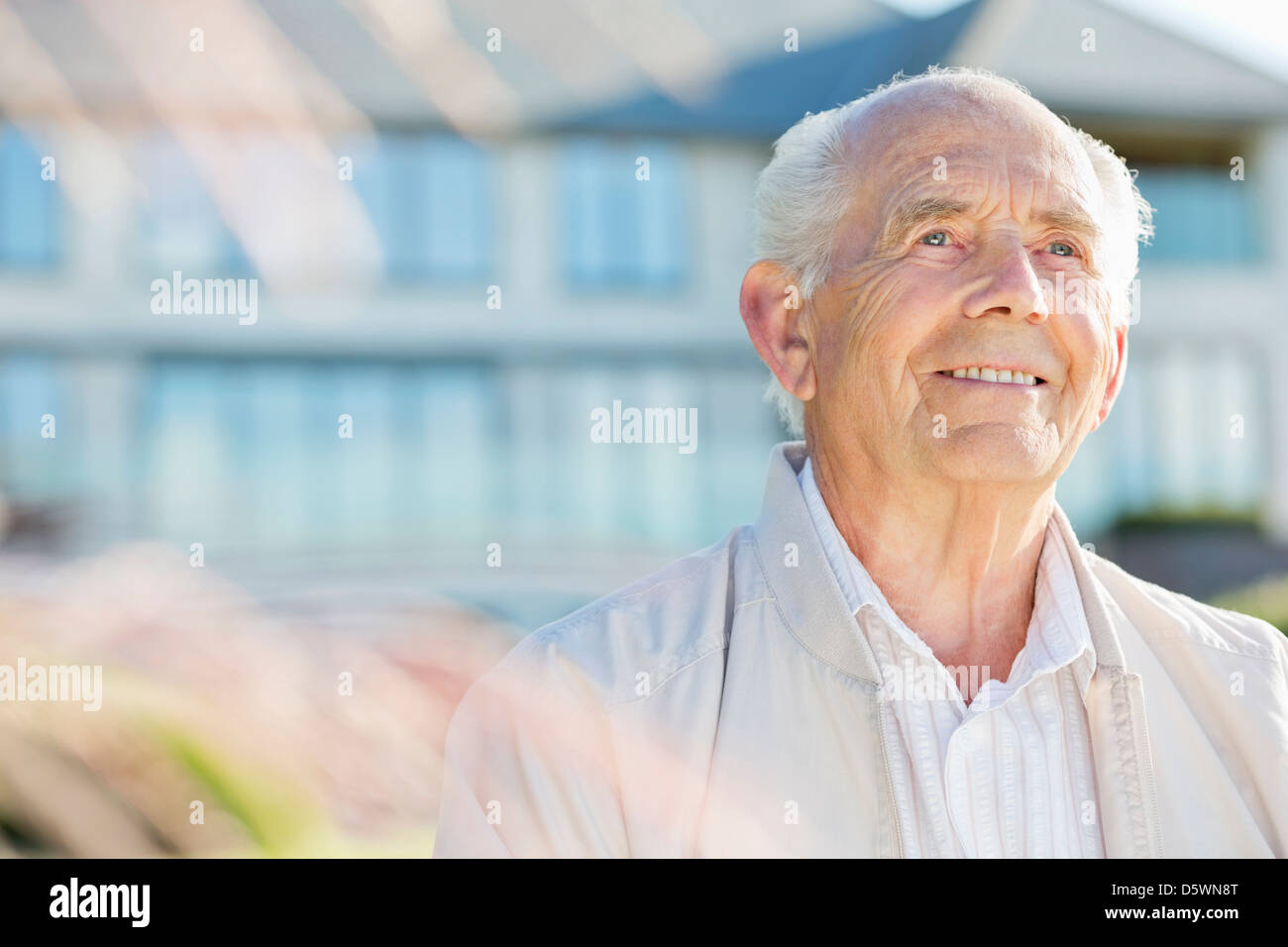 Smiling older man standing outdoors - Stock Image