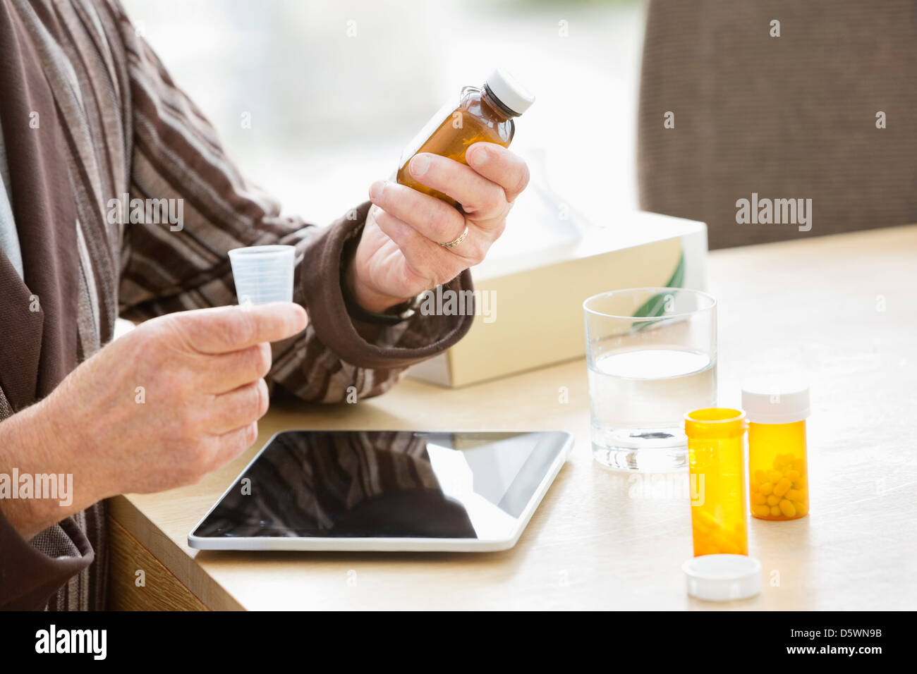Older man taking medications at table - Stock Image