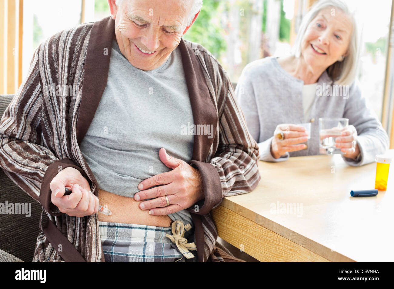 Older man giving himself injection - Stock Image