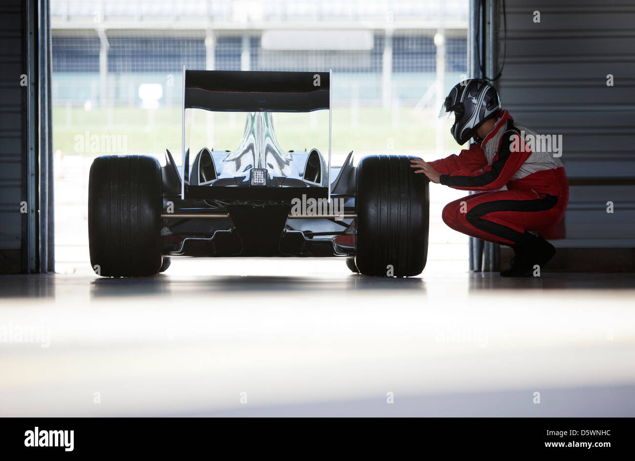 Racer working on car in garage - Stock Image