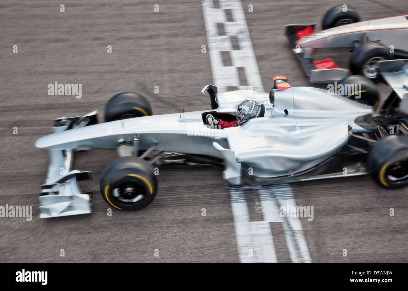Race car crossing finish line on track Stock Photo